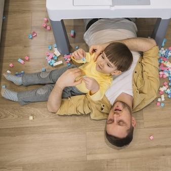 Figlio e padre di alta vista che pongono sul pavimento