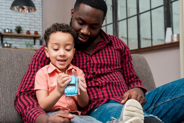 Figlio e padre neri che si siedono con la piccola automobile del giocattolo