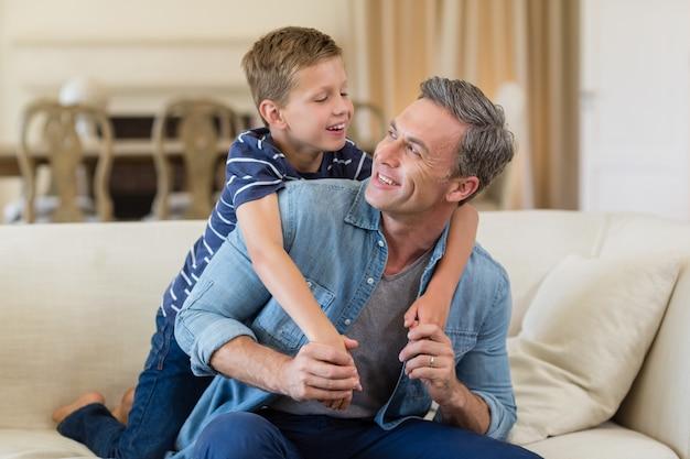 Figlio sorridente che abbraccia un padre in salone