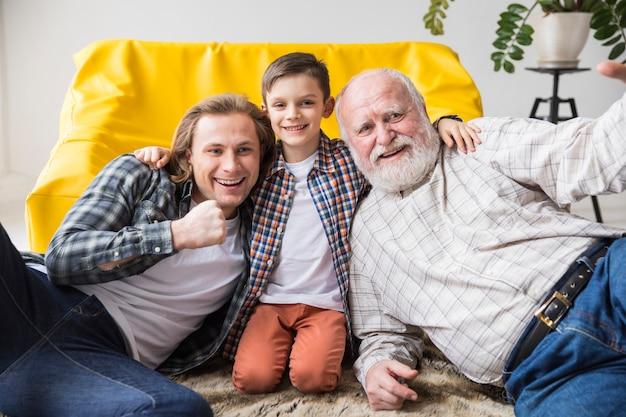 Figlio sveglio allegro che abbraccia papà e nonno