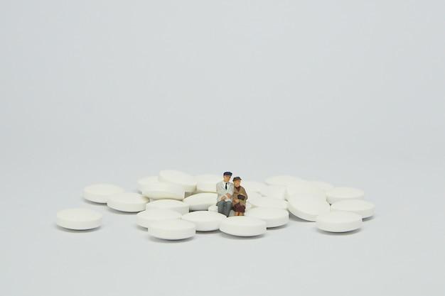 Figura anziana delle coppie che si siede su un mucchio delle pillole bianche.