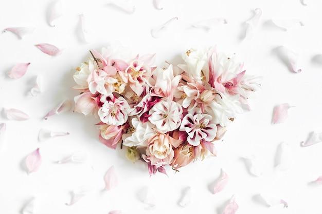 Figura del cuore fatta dei fiori su fondo bianco nella disposizione piana