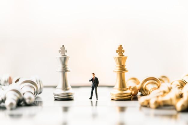 Figura del piccolo imprenditore che sta e che cammina sulla scacchiera con i pezzi degli scacchi.