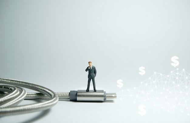 Figura dell'uomo d'affari che sta sul cavo del tipo c di usb usb. concetto di commercio elettronico.