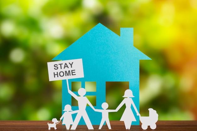 Figura di carta di una coppia che si tiene per mano con i bambini. casa blu e sfondo sfocato.