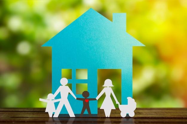 Figura di carta di una coppia che si tiene per mano con i bambini e un figlio nero adottivo. casa blu e sfondo sfocato. diversità, concetto di minoranze.