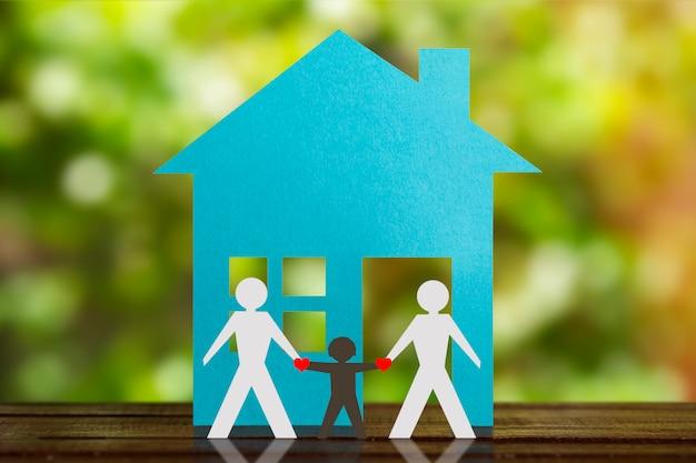 Figura di carta di una coppia gay che si tiene per mano con il figlio adottivo. casa blu e sfondo denocato. diversità, concetto di minoranze.
