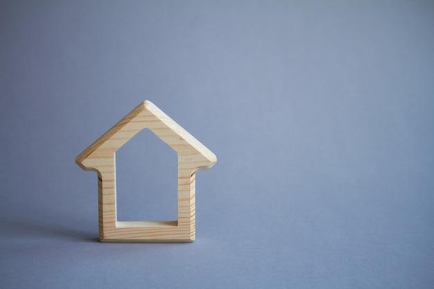 Figura di casa in legno su grigio, eco-compatibile con l'ambiente