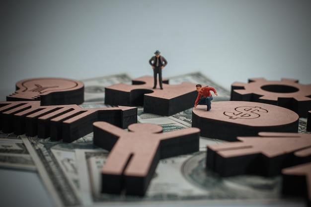 Figura di legno con le icone di affari nel concetto di finanza.