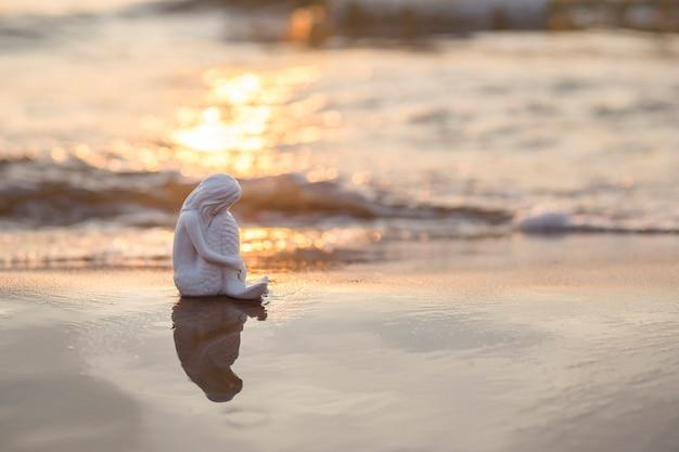 Figura di sirena seduta sulla sabbia in riva al mare
