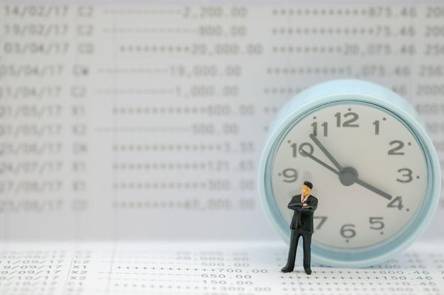 Figura miniatura dell'uomo d'affari che si leva in piedi sul libretto di banca con l'orologio rotondo.