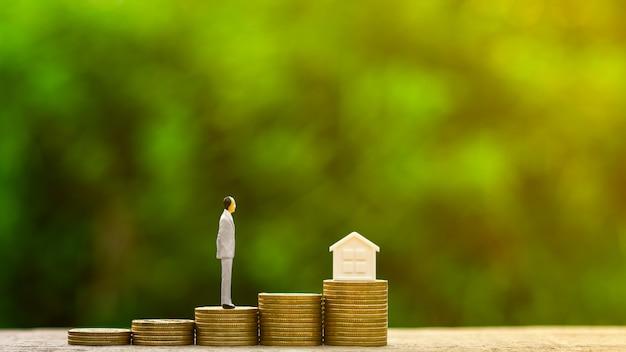 Figura miniatura dell'uomo d'affari che si leva in piedi sulla pila di monete dorate