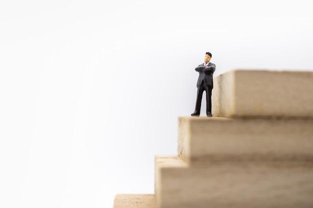 Figura miniatura dell'uomo d'affari che sta sulla pila di pila della scala del blocco di legno di blocco di legno