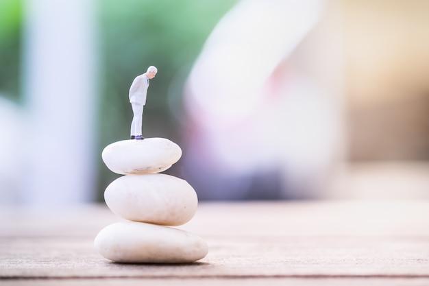 Figura miniatura dell'uomo d'affari che sta sulla pila instabile di rocce bianche sulla tavola di legno