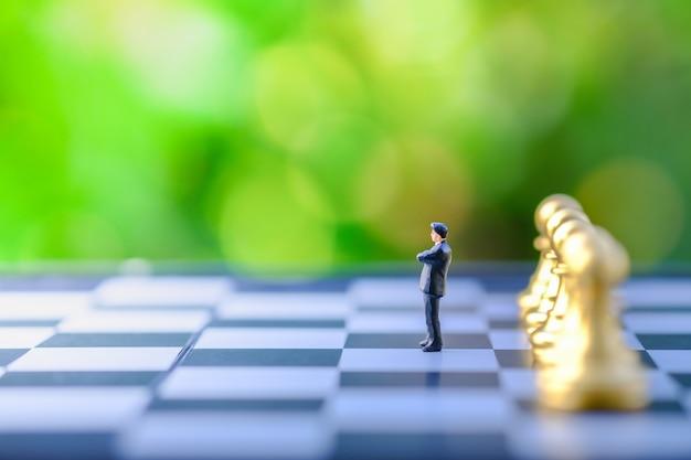 Figura miniatura dell'uomo d'affari che sta sulla scacchiera con i pezzi degli scacchi dorati