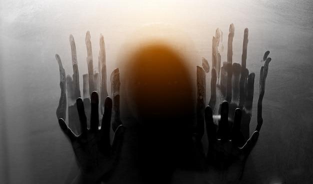 Figura oscura dietro il vetro. concetto di paura e panico.