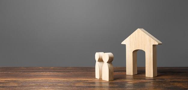Figure di persone guardano la casa. alloggio comodo ed economico.
