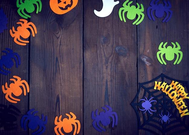 Figure di ragno in feltro multicolore, ragnatela su legno marrone