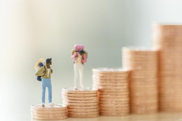 Figure di viaggiatore in miniatura di due uomini e donna con zaino in piedi sulla pila di monete