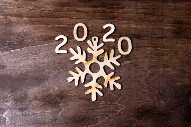 Figure in legno 2020 e fiocco di neve su uno sfondo di legno scuro. vista dall'alto