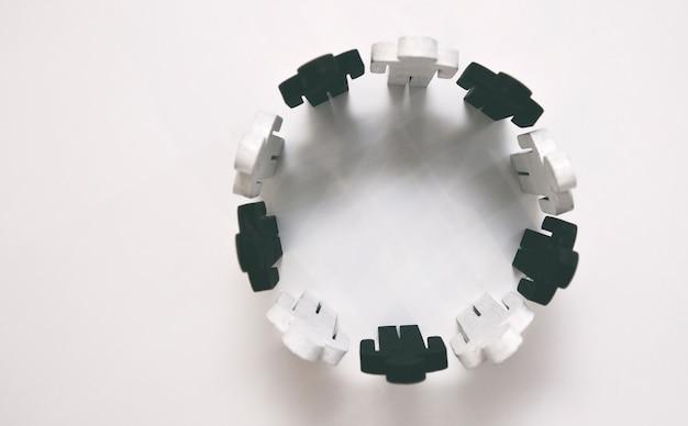 Figure in legno di colore bianco e nero di persona stanno in cerchio