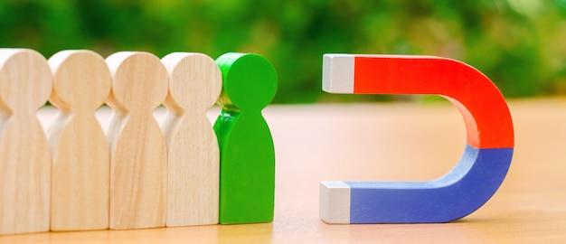 Figure in legno di persone e un magnete.