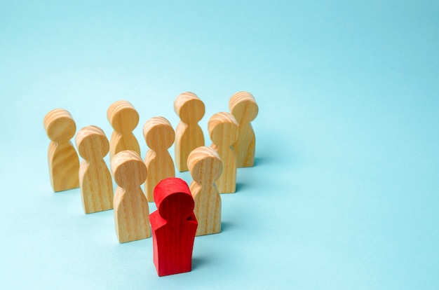 Figure in legno di persone. il capo del team aziendale indica la direzione