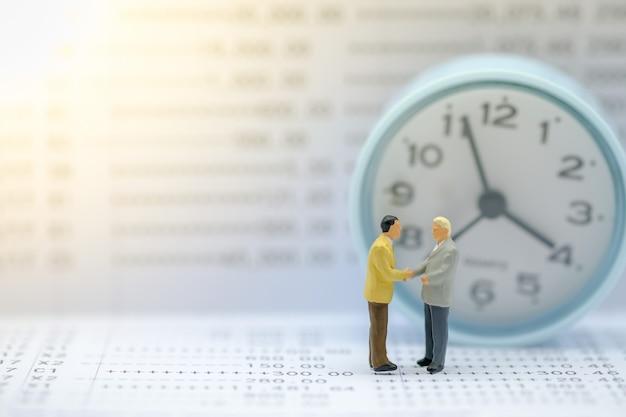 Figure in miniatura dell'uomo d'affari in piedi sul libretto di banca con orologio rotondo.