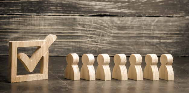 Figure umane in legno si uniscono accanto a un segno di spunta nella casella. il concetto di elezioni