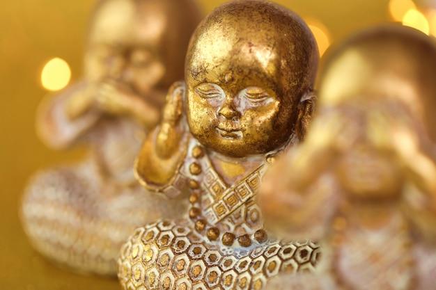 Figurina del monaco d'oro impostata su dorato con bokeh dorato offuscata