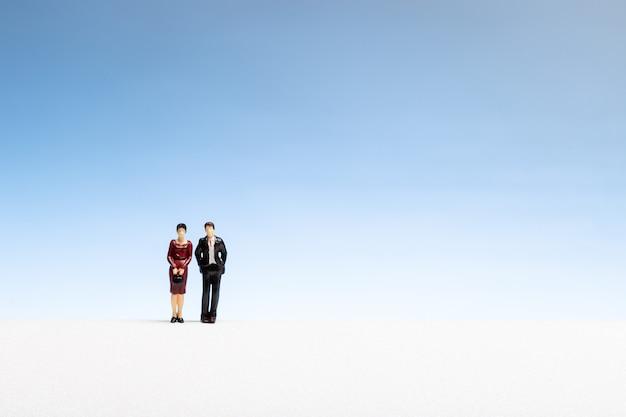 Figurina della donna e dell'uomo sul copyspace di pendenza. concetto di coppia o matrimonio