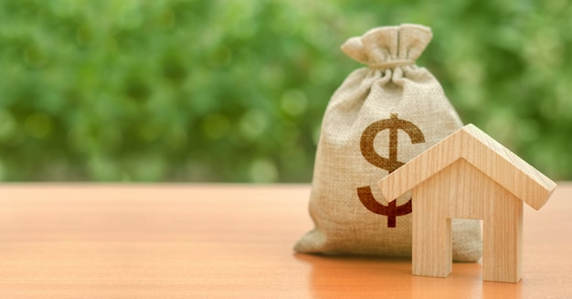 Figurina di casa in legno e borsa di denaro con un simbolo del dollaro. bilancio, fondi sovvenzionati