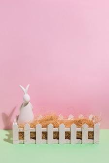 Figurina di coniglio bianco con fieno in scatola sul tavolo