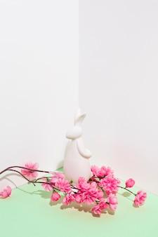 Figurina di coniglio bianco con ramo di fiori sul tavolo