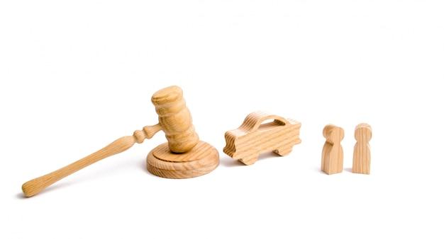 Figurina di legno di un'auto con le persone in un martello del giudice su uno sfondo bianco.