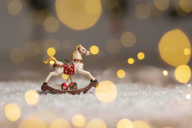 Figurina di un cavallo a dondolo decorazioni festive, calde luci bokeh.