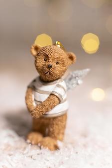Figurina di un simpatico orso con ali d'angelo decorazioni festive, luci calde del bokeh.