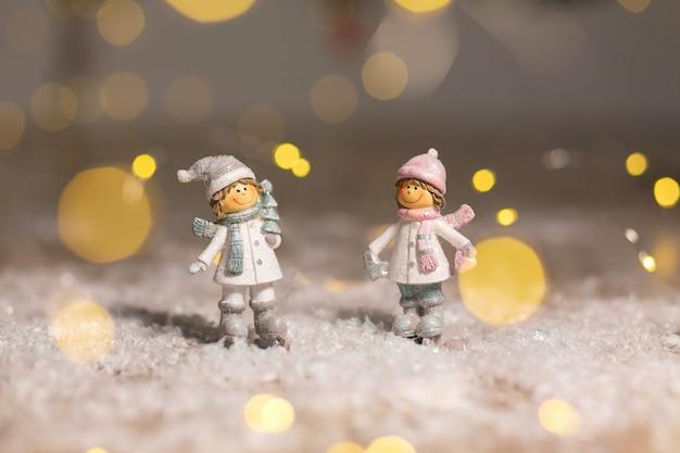 Figurine decorative a tema natalizio. statuetta ragazzo e ragazza in cappelli e sciarpe lavorati a maglia