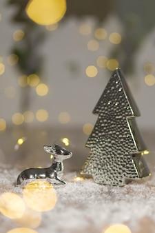 Figurine decorative di un tema natalizio. statuetta di un cervo sdraiato vicino a un albero di natale. decorazioni festive, calde luci bokeh.