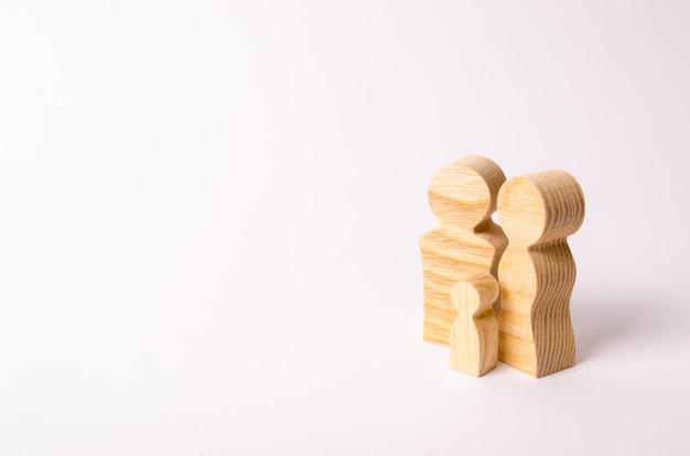 Figurine di legno di una giovane famiglia su uno sfondo bianco.