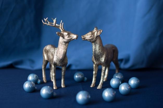 Figurine dorate della renna di natale con le decorazioni su priorità bassa blu