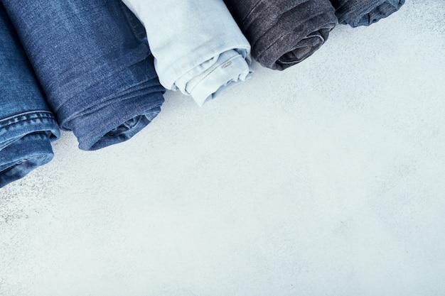 Fila dei jeans rotolati differenti su fondo bianco