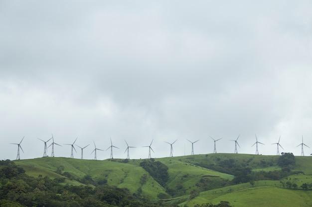 Fila del mulino a vento sulla cima verde della montagna alla costa rica