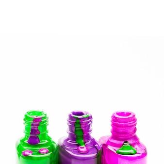 Fila della bottiglia colorata dello smalto colorato aperta su fondo bianco