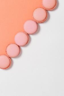 Fila di amaretti su sfondo colorato con spazio di copia. biscotti rotondi saporiti arancioni. stile minimal.