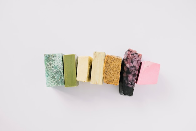 Fila di barre di sapone colorate su sfondo bianco