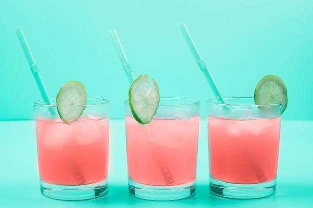 Fila di bicchieri da cocktail con cubetti di ghiaccio; cannuccia; fette di limone su sfondo di menta