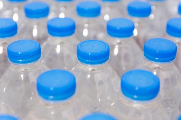 Fila di bottiglie d'acqua. bottiglie con tappi blu per acqua potabile