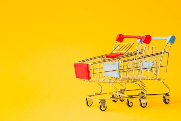 Fila di carrelli del supermercato con maniglie rosse e blu