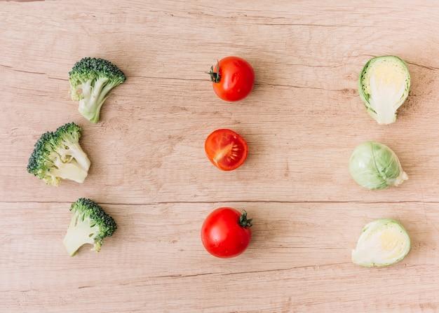 Fila di cavoletti di bruxelles; broccoli e pomodorini sullo sfondo in legno